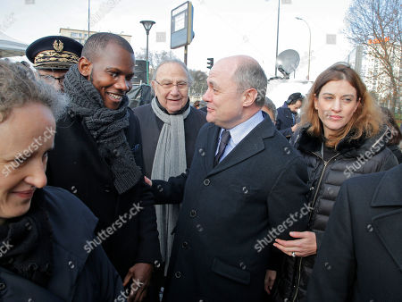 French Interior Minister Bruno Leroux, center, talks to Lassana Bathily, left, during a ceremony at the place of the terrorist attack at the kosher supermarket to mark the second anniversary of the attacks, . State Secretary in charge of Victims Juliette Meadel, right. Lassana Bathily saved several Jewish shoppers during the attack by hiding them in the kosher market's basement