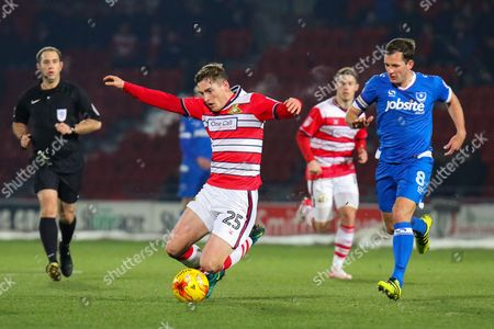 Doncaster midfielder Conor Grant is brought down by Portsmouth midfielder Michael Doyle with the ball during the EFL Sky Bet League 2 match between Doncaster Rovers and Portsmouth at the Keepmoat Stadium, Doncaster