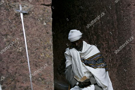 Ethiopian Orthodox Priest Reads the Psalm of David On the Outside Walls of Bet Medhanealem Monolithic Church Hewn out of Solid Rock in the 12th Century Ad in the Northern City of Lalibela Ethiopia On 11 September 2007 There Are More Than 26 Rock Hewn Structures in the Lalibela Region From Basic Caves Structures to the Impressive St George Church All Built During the Height of Medieval Ethiopian Cilvilization During the 9th to 12th Cenury Ad Due to a Quirk in the Orthodox Christian Calender of Ethiopia the Country Will Celebrate the Year 2000 - 7 Years 7 Months and 7 Days Behind Most of the Rest of the World at Midnight On 11 September 2007 But Event Cancelations On Security Grounds Have Taken the Shine Off the Millennium Festivities For Many