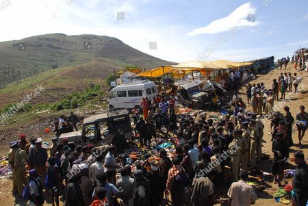Local People Gather and Look at the Overturned Vehicles and Belongings of Pilgrims at the Site of a Pilgrimage Stampede About 50 Miles (80 Kilometres Northeast From the Famed Hindu Shrine of Sabarimala in the Southern Indian State of Kerala on 15 January 2011 at Least 104 People Died in a Stampede During a Pilgrimage to the Hindu Shrine of Sabarimala in the Southern Indian State of Kerala Officials Said 15 January Pilgrims Were Returning From the Shrine Down a Hillside Late Friday when a Vehicle Lost Control and Crashed Into the Crowd Triggering the Stampede Kerala Home Secretary Jai Kumar Said the Accident Took Place in a Densely Forested Hilly Terrain on a Path Leading to the Shrine So Far 74 of the Victims Have Been Identified India Sabarimala
