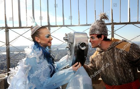 Stock Image of Elena Lev (l) a Hoops Performer From the Cirque Du Soleil Show 'Wintuk' and a Fellow Cast Member Joke Around with a Set of Binoculars While Performing on the Observation Deck of the Empire State Building in New York New York Usa 19 November 2010 Members of the Cast of the Show Made an Appearance at the Empire State Building to Promote the Opening Night of the Winter Themed Show United States New York