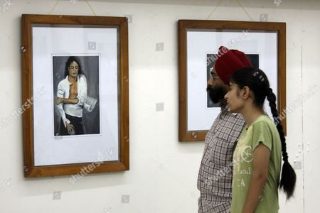 Indian Visitors Have a Look at One of 26 Paintings and Graphic Illustrations of Late Us Singer Michael Jackson Put on Display During an Exhibition by Indian Student and Artist Lakshit Sharma (unseen) on the Occasion of Michael Jackson's 52nd Birth Anniversary in the Northern Indian City of Amritsar 29 August 2010 Lakshit a Student of Spring Dale Senior School Said the Exhibition is a Form of Tribute to the Greatest Pop Icon Through Which He Has Tried to Capture the Varied Persona of Him India Amritsar