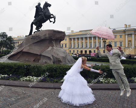 A Russian Groom Jumps to His Wife During a Wedding Ceremony Near the Statue of Peter the Great the Bronze Horseman Monument by Etienne Maurice Falconet in St Petersburg Russia 26 June 2010 Russian Federation St.petersburg