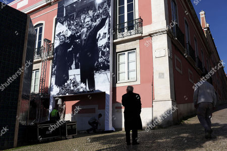 Stock Photo of Workers place a portrait of former Socialist party leader Mario Soares and his wife Maria Barroso on the facade of the party headquarters in Lisbon . Soares, a former prime minister and president of Portugal who helped steer his country toward democracy after a 1974 military coup and grew into a global statesman through his work with the Socialist International movement died Saturday at 92. A state funeral will be held Tuesday