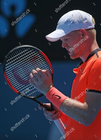 Britain's Kyle Edmund grabs at his racket after missing a shot to Australia's Matthew Barton during their men's singles match at the Sydney International tennis tournament in Sydney