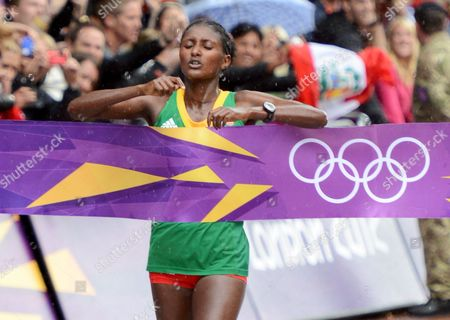Ethioia's Tiki Gelana Crosses the Finish Line in the Womens Marathon and Wins the Gold Medal During the London 2012 Olympic Games Athletics Track and Field Events at the Olympic Stadium London Britain 05 August 2012 United Kingdom London