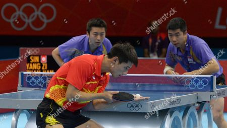 Jike Zhang (red R) and Hao Wang (not in Picture) of China Compete Against Zi Yang (purple L) and Jian Zhan of Singapore in the Men's Table Tennis Team Quarterfinals During the London 2012 Olympic Games London Britain 05 August 2012 United Kingdom London