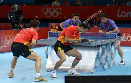 Jike Zhang (red R) and Hao Wang of China Compete Against Zi Yang (purple L) and Jian Zhan of Singapore in the Men's Table Tennis Team Quarterfinals During the London 2012 Olympic Games London Britain 05 August 2012 United Kingdom London