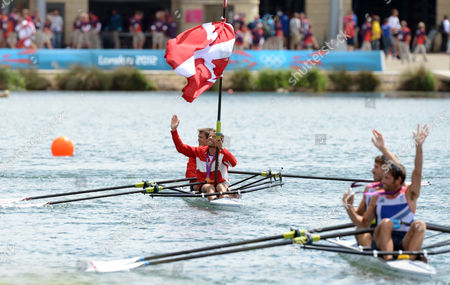 Denmark's Rasmus Quist and Mads Rasmussen (c) Celebrate with the Danish Flag After Winning the Gold Medal and Britain's Mark Hunter and Zac Purchase (r) Waves After Winning Silver in the Lightweight Men's Duoble Sculls Final During the London 2012 Olympic Games Rowing Competition at the Eton Dorney Rowing Centre Near the Village of Dorney West of London Britain 04 August 2012 United Kingdom Dorney