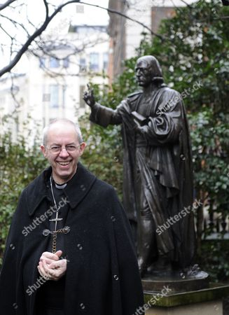 The Archbishop of Canterbury Justin Welby (c) Stands in Front of the Statue of Anglican Cleric John Wesley in the Gardens of St Paul's Cathedral As He Conducts a 'Journey in Prayer' From the City of London to Southwark Cathedral London Britain 16 March 2013 United Kingdom London