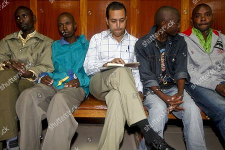 Former First Secretary at the Venezuelan Embassy in Kenya Dwight Sagaray (c) Reads a Book by Paulo Coelho As He Waits with Other Suspected Felons to Be Called in at a Courtroom in Nairobi Kenya 29 October 2012 Sagaray who is Charged with the Murder of Venezuela's Charge D'affaires and Acting Ambassador Olga Fonseca was Denied Bail on 29 October Fonseca was Found Strangled to Death on 27 July 2012 at Her Official Residence in Nairobi Kenya Nairobi