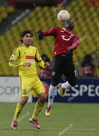 Yuri Zhirkov (l) of Anzhi Makhachkala Vies For the Ball with Didier Ya Konan (r) of Hanover 96 During the Uefa Europa League Soccer Match Between Anzhi Makhachkala and Hanover 96 at the Luzhniki Stadium in Moscow Russia 14 February 2013 Russian Federation Moscow