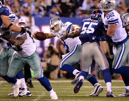 The Cowboys' Tony Romo (c) Escapes Pressure by the Giants' Keith Rivers (r) During the First Half of the Game Between the Dallas Cowboys and the New York Giants at Metlife Stadium in East Rutherford New Jersey Usa 05 September 2012 United States East Rutherford