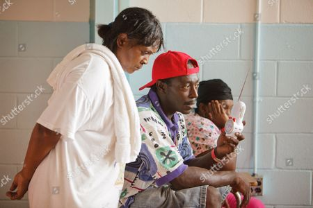 Stock Image of Lily Cryer (l) and Kenneth Watson (c) Listen to the Radio For News Reports As Residents Under an Emergency Evacuation Order Flee Potential Floodwaters in Low Lying Areas Near the Tangipahoa River in Kentwood Louisiana Usa 30 August 2012 Constant Wind and Rain From Ex Hurricane Isaac Has Cut Power to Hundreds of Thousands of Homes and Businesses and Forced Many People From Their Homes United States Kentwood