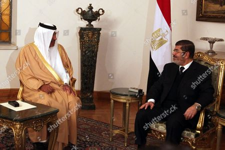 Egyptian President Mohamed Morsi (r) Meets with Qatari Prime Minister Hamad Bin Jasim Bin Jabir Al Thani (l) in the Presence of Egyptian Prime Minister Hisham Qandil (not Pictured) at the Presidential Palace in Cairo Egypt 08 January 2013 According to Media Reports on 08 January Qatar Confirmed It Would Lend Egypt's Government an Additional 2 Billion Dollars and Grant It an Extra 500 Million Dollars Outright Extending a Lifeline As the Government Battles to Contain a Currency Crisis Egypt Cairo