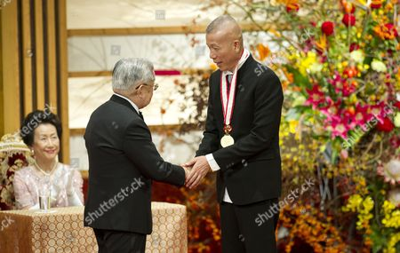 Japanese Prince Hitachi (l) Shakes Hands with Chinese Artist Cai Guo-qiang During the Praemium Imperiale Awards Ceremony in Tokyo Japan 23 October 2012 the Award is Presented Annually by the Japan Art Association For Painting Architecture Sculpture Music and Theater/film Japan Tokyo