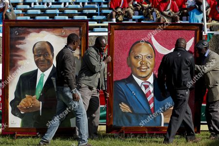Stock Image of Workers Move a Portrait of Kenya's President Uhuru Kenyatta (r) Next to a Portrait of Outgoing President Mwai Kibaki (l) During Kenyatta's Inauguration Ceremony in Kasarani on the Outskirts of the Capital Nairobi Kenya 09 April 2013 Kenyatta was Sworn in As the Country's Fourth President on 09 April at a Stadium Filled with Tens of Thousands of Cheering Supporters Despite the Charges He Faces at the International Criminal Court (icc) For the Crimes Against Humanity Kenya Nairobi