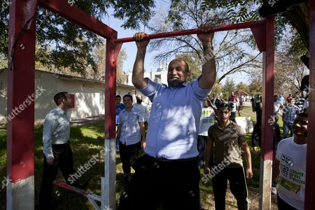 Holding His 'Kippa ' Or Yamulka with His Teeth Naftali Bennett Leader of the Habayit Hayehudit (the Jewish House) Party Does Chin-ups Outside a Religious Seminary Or 'Yeshiva ' in Shapiro Israel in a Final Campaigning Stop 20 January 2013 Bennet was Speaking to Religious Students who Face Army Induction and was Looking For Their Votes As Well As Urging Them to Settle in Religious Areas in the West Bank General Elections in Israel Are Scheduled to Be Held on 22 January Israel Shapiro