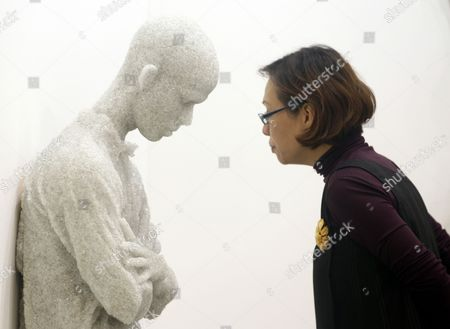 A Woman Views a Broken Glass and Resin Sculpture Entitled 'Figure with Arms Crossed' by Us Artist Daniel Arsham During a Preview of Art Stage Singapore at the Marina Bay Sands in Singapore 23 January 2013 Art Stage Singapore Runs From 24 to 27 January Singapore Singapore
