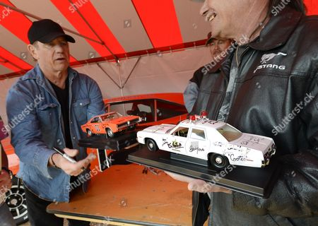 Us Actor Tom Wopat (l) of the Television Show the Dukes of Hazzard Signs Model Cars For a Fan During a Reunion at the Old Middle Georgia Speedway in Byron Georgia Usa 09 March 2013 the Dukes of Hazzard Aired on Cbs From 1979 to 1985 and was Based on the Fictional Hazzard County Georgia Wopat Played Luke Duke on the Show United States Byron