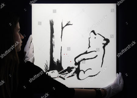 A Bonhams Employee Poses For Photographs in Front of the Artwork 'Winnie the Pooh' by British Artist Banksy During the Bonhams Urban Art Sale Preview in London Britain 09 August 2012 a Striking Selection of Urban Art From Banksy Bleck Le Rat Nick Walker Among Other Artists is Presented Ahead of the Los Angeles Art Urban Sale on 29 October 2012 United Kingdom London