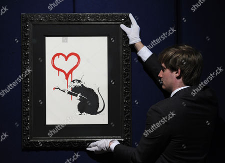 A Bonhams Employee Poses For Photographs in Front of the Artwork 'Love Rat' by British Artist Banksy During the Bonhams Urban Art Sale Preview in London Britain 09 August 2012 a Striking Selection of Urban Art From Banksy Bleck Le Rat Nick Walker Among Other Artists is Presented Ahead of the Los Angeles Art Urban Sale on 29 October 2012 United Kingdom London