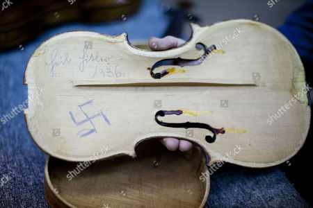 Stock Picture of Amnon Weinstein a Holocaust Violin Collector Holds a Violin with a Handwritten Swastika Inside and the Words 'Heil Hitler' and the Year 1936 Which He Received Recently From Us Violin Maker Josh Henry of Washington Dc in His Workshop in Tel Aviv Israel 07 April 2013 Weinstein a Second Generation Israeli Violin Maker Has a Collection of More Than 45 Violins From the Holocaust Period Which He Has Collected Over the Last 20 Years Israel Marks Holocaust Remembrance Day For Twenty-four Hours Beginning This Evening Remembering the 6-million Jews who Perished in the Holocaust of World War Ii Israel Tel Aviv
