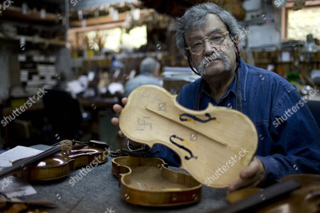 Stock Photo of Amnon Weinstein a Holocaust Violin Collector Holds a Violin with a Handwritten Swastika Inside and the Words 'Heil Hitler' and the Year 1936 Which He Received Recently From Us Violin Maker Josh Henry of Washington Dc in His Workshop in Tel Aviv Israel 07 April 2013 Weinstein a Second Generation Israeli Violin Maker Has a Collection of More Than 45 Violins From the Holocaust Period Which He Has Collected Over the Last 20 Years Israel Marks Holocaust Remembrance Day For Twenty-four Hours Beginning This Evening Remembering the 6-million Jews who Perished in the Holocaust of World War Ii Israel Tel Aviv