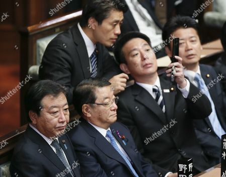 Stock Photo of Japanese Prime Minister Yoshihiko Noda (l Bottom) Attends the General Assembly As Seiji Maehara (2nd R) Minister For National Policy Shows His Mobile Phone to Goshi Hosono (standing) the Policy Chief of the Ruling Democratic Party of Japan at Japan's Lower House in Tokyo Japan 16 November 2012 Noda Talked in a Parliamentary Debate November 14 with the Biggest Opposition Liberal Democratic Party President Shinzo Abe That He Would Dissolve the Lower House on November 16 if Opposition Parties Would Agree Electoral Reforms Foreign Minister Koichiro Gemba is on the Right and Chief Cabinet Secretary Osamu Fujimura is Seen on the Second Left in the Bottom Japan Tokyo