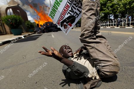 A Kenyan Activist Reacts After Setting Mock Coffins Alight in Front of the Parliament Building During a Demonstration to Protest Against Lawmakers who Passed the Bill to Award Themselves Some 110 000 Us Dollars (82 887 Euro) Sendoff Bonus in Nairobi Kenya 16 January 2013 on Top of a Hefty Bonus the Proposed Bill Would Have Granted Outgoing Members of Parliament who Are Already Some of the Best Paid on the Continent Bodyguards For Life Diplomatic Passports Unlimited Access to the Vip Lounges at All Kenyan Airports and State Funerals Kenyan President Mwai Kibaki Has Declined to Assent to the Bill While Approving a Bill Awarding Himself Almost 300 000 Us Dollars (226 044 Euro) Sendoff Package Kenya Nairobi