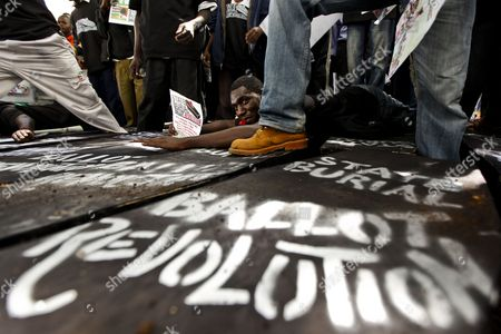A Kenyan Activist Flops Over a Mock Coffin During a Demonstration to Protest Against Lawmakers who Passed the Bill to Award Themselves Some 110 000 Us Dollars Sendoff Bonus in Nairobi Kenya 16 January 2013 on Top of a Hefty Bonus the Proposed Bill Would Have Granted Outgoing Members of Parliament who Are Already Some of the Best Paid on the Continent Bodyguards For Life Diplomatic Passports Unlimited Access to the Vip Lounges at All Kenyan Airports and State Funerals Kenyan President Mwai Kibaki Has Declined to Assent to the Bill While Approving a Bill Awarding Himself Almost 300 000 Us Dollars Sendoff Package Kenya Nairobi