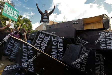 A Kenyan Activist Stands on Top of Mock Coffins Piled Up Before Setting Them Alight in Front of the Parliament Building During a Demonstration to Protest Against Lawmakers who Passed the Bill to Award Themselves Some 110 000 Us Dollars (82 887 Euro) Sendoff Bonus in Nairobi Kenya 16 January 2013 on Top of a Hefty Bonus the Proposed Bill Would Have Granted Outgoing Members of Parliament who Are Already Some of the Best Paid on the Continent Bodyguards For Life Diplomatic Passports Unlimited Access to the Vip Lounges at All Kenyan Airports and State Funerals Kenyan President Mwai Kibaki Has Declined to Assent to the Bill While Approving a Bill Awarding Himself Almost 300 000 Us Dollars (226 044 Euro) Sendoff Package Kenya Nairobi