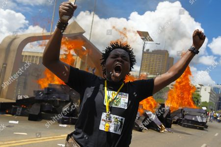 A Kenyan Activist Reacts After Setting Mock Coffins Alight in Front of the Parliament Building During a Demonstration to Protest Against Lawmakers who Passed the Bill to Award Themselves Some 110 000 Us Dollars Sendoff Bonus in Nairobi Kenya 16 January 2013 on Top of a Hefty Bonus the Proposed Bill Would Have Granted Outgoing Members of Parliament who Are Already Some of the Best Paid on the Continent Bodyguards For Life Diplomatic Passports Unlimited Access to the Vip Lounges at All Kenyan Airports and State Funerals Kenyan President Mwai Kibaki Has Declined to Assent to the Bill While Approving a Bill Awarding Himself Almost 300 000 Us Dollars Sendoff Package Kenya Nairobi