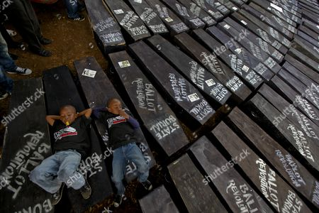 Kenyan Children Lay Down on Mock Coffins During a Demonstration to Protest Against Lawmakers who Passed the Bill to Award Themselves Some 110 000 Us Dollars Sendoff Bonus in Nairobi Kenya 16 January 2013 on Top of a Hefty Bonus the Proposed Bill Would Have Granted Outgoing Members of Parliament who Are Already Some of the Best Paid on the Continent Bodyguards For Life Diplomatic Passports Unlimited Access to the Vip Lounges at All Kenyan Airports and State Funerals Kenyan President Mwai Kibaki Has Declined to Assent to the Bill While Approving a Bill Awarding Himself Almost 300 000 Us Dollars Sendoff Package Kenya Nairobi