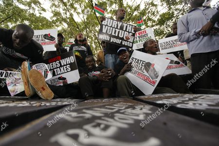 Kenyan Activists Sit on Mock Coffins and Hold Placards During a Demonstration to Protest Against Lawmakers who Passed the Bill to Award Themselves Some 110 000 Us Dollars Sendoff Bonus in Nairobi Kenya 16 January 2013 on Top of a Hefty Bonus the Proposed Bill Would Have Granted Outgoing Members of Parliament who Are Already Some of the Best Paid on the Continent Bodyguards For Life Diplomatic Passports Unlimited Access to the Vip Lounges at All Kenyan Airports and State Funerals Kenyan President Mwai Kibaki Has Declined to Assent to the Bill While Approving a Bill Awarding Himself Almost 300 000 Us Dollars Sendoff Package Kenya Nairobi