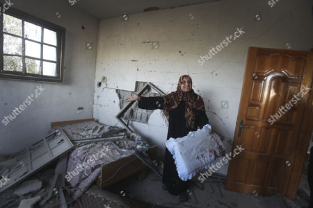 A Palestinian Woman Inspects the Damage to Her House After an Israeli Airstrike in Beit Hanoun North Gaza Strip on 16 November 2012 Reports State That Missiles Continue to Be Fired on Israeli Targets by Palestinian Militant in the Gaza Strip As Israel Continues to Strike Targets in Retaliation Inside the Gaza Strip on the Second Day of Operation Pillar Cloud Following the Assassination of Hamas Militant Leader Ahmed Jabari Israeli Forces Launched a Heavy Barrage of Bombs at the Break of Dawn But Also Announce a Three Hours Ceasefire During the Visit of the Egyptian Prime Minister Hesham Qandil in the Gaza Strip - Gaza Strip