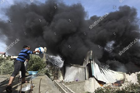 Palestinian People Try to Extinguish Fire After an Israeli Airstrike on a Wood Factory in East Jabaliya North Gaza Strip on 16 November 2012 Reports State That Missiles Continue to Be Fired on Israeli Targets by Palestinian Militant in the Gaza Strip As Israel Continues to Strike Targets in Retaliation Inside the Gaza Strip on the Second Day of Operation Pillar Cloud Following the Assassination of Hamas Militant Leader Ahmed Jabari Israeli Forces Launched a Heavy Barrage of Bombs at the Break of Dawn But Also Announce a Three Hours Ceasefire During the Visit of the Egyptian Prime Minister Hesham Qandil in the Gaza Strip - Gaza Strip