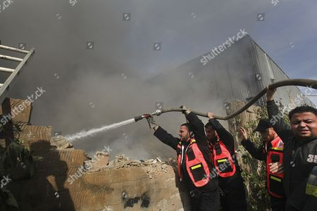 Palestinian Firefighters Try to Extinguish Fire After an Israeli Airstrike on a Wood Factory in East Jabaliya North Gaza Strip on 16 November 2012 Reports State That Missiles Continue to Be Fired on Israeli Targets by Palestinian Militant in the Gaza Strip As Israel Continues to Strike Targets in Retaliation Inside the Gaza Strip on the Second Day of Operation Pillar Cloud Following the Assassination of Hamas Militant Leader Ahmed Jabari Israeli Forces Launched a Heavy Barrage of Bombs at the Break of Dawn But Also Announce a Three Hours Ceasefire During the Visit of the Egyptian Prime Minister Hesham Qandil in the Gaza Strip - Gaza Strip