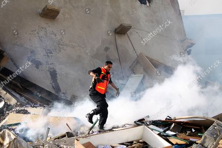 A Palestinian Firefighter Try to Extinguish a Fire Among the Rubbles of a Destroyed Hamas Ministry of Interior Building After an Israeli Air Strike in Gaza City on 16 November 2012 Missiles Continue to Be Fired on Israeli Targets by Palestinian Militant in the Gaza Strip As Israel Continues to Strike Targets in Retaliation Inside the Gaza Strip on the Second Day of Operation Pillar Cloud Following the Assassination of Hamas Militant Leader Ahmed Jabari Israeli Forces Launched a Heavy Barrage of Bombs at the Break of Dawn But Also Announce a Three Hours Ceasefire During the Visit of the Egyptian Prime Minister Hesham Qandil in the Gaza Strip - Gaza City