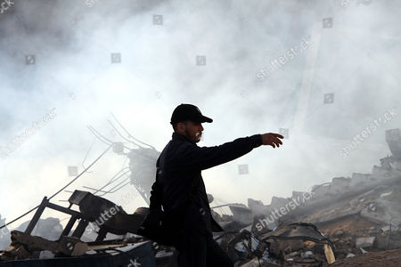 Stock Photo of A Palestinian Hamas Member Inspects a Destroyed Hamas Ministry of Interior Building After an Israeli Air Strike in Gaza City on 16 November 2012 Missiles Continue to Be Fired on Israeli Targets by Palestinian Militant in the Gaza Strip As Israel Continues to Strike Targets in Retaliation Inside the Gaza Strip on the Second Day of Operation Pillar Cloud Following the Assassination of Hamas Militant Leader Ahmed Jabari Israeli Forces Launched a Heavy Barrage of Bombs at the Break of Dawn But Also Announce a Three Hours Ceasefire During the Visit of the Egyptian Prime Minister Hesham Qandil in the Gaza Strip - Gaza City