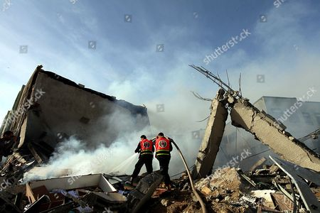 Palestinian Firefighters Try to Extinguish a Fire in a Destroyed Hamas Ministry of Interior Building After an Israeli Air Strike in Gaza City on 16 November 2012 Missiles Continue to Be Fired on Israeli Targets by Palestinian Militant in the Gaza Strip As Israel Continues to Strike Targets in Retaliation Inside the Gaza Strip on the Second Day of Operation Pillar Cloud Following the Assassination of Hamas Militant Leader Ahmed Jabari Israeli Forces Launched a Heavy Barrage of Bombs at the Break of Dawn But Also Announce a Three Hours Ceasefire During the Visit of the Egyptian Prime Minister Hesham Qandil in the Gaza Strip - Gaza City