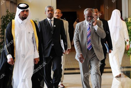 Sudanese Foreign Minister Ali Karti (r) Tlaks on His Mobile Phone As He Arrives to Attend the Ministerial Meeting of the Arab Peace Initiative Committee in Doha Qatar on 09 December 2012 the Meeting Will Focus on the Arab Position Regarding the Peace Process and the Palestinian Reconciliation Qatar Doha