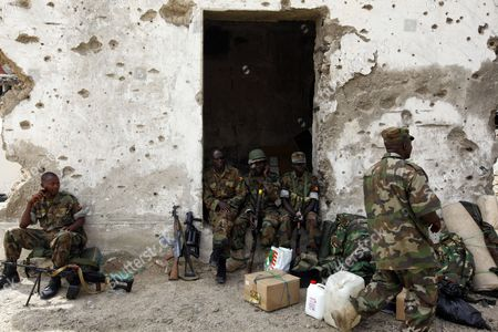 Ugandan Soldiers of the African Union Forces Rest at Ruins of a Building in the Capital Mogadishu Somalia 07 August 2012 Un Secretary-general's Special Representative and Head of the Un Political Office For Somalia (unpos) Augustine Mahiga Has Urged Somali Leaders to Ensure That the Remaining Key Issues Are Resolved to Complete the Country's Political Transition Process Before the Deadline of 20 August 2012 Prime Minister of Somalia Abdiweli Mohamed Ali Announced on 07 August His Candidacy For the Country's Upcoming Presidential Election Somalia on 06 August 2012 Marked One Year Since the African Union and Somali Government Forces Had Driven out the Hardline Islamist Militants Al-shabab From the Capital Mogadishu on 06 August 2011 Somalia Mogadishu