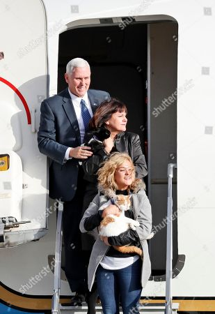 """Mike Pence, Karen Pence, Charlotte Pence Vice President-elect Mike Pence steps off an Air Force plane similar to the one he will use after being sworn in, as he, his wife Karen Pence, center, holding cat """"Oreo,"""" and daughter Charlotte Pence holding """"Pickle,"""" arrive at Andrews Air Force Base, Md"""
