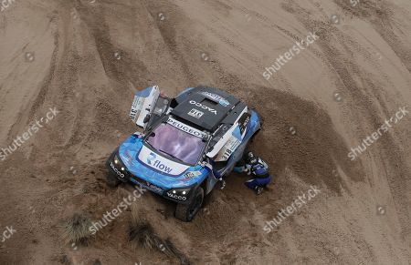 Romain Dumas, Alain Guehennec Driver Romain Dumas and co-driver Alain Guehennec, both of France, work to get their Peugeot traction in the sand during the 7th stage of the Dakar Rally between Oruro and Uyuni, Bolivia, . The race started in Paraguay and passes through Argentina as well