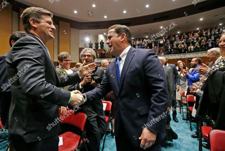 Arizona Republican Gov. Doug Ducey, center, shakes hands with Phoenix Mayor Greg Stanton, left, as he arrives to give his State of the State Address, opening the Arizona state legislature, in Phoenix
