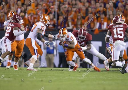 Clemson tight end Jordan Leggett (16) run with the ball after the catch as Alabama defensive lineman Dalvin Tomlinson (54) makes the tackle during College Football Playoff National Championship game action between the Alabama Crimson Tide and the Clemson Tigers at Raymond James Stadium in Tampa Bay, Florida. Clemson defeated Alabama 35-31