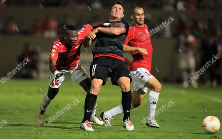 Cristian Rodriguez (c) of Atletico Madrid Vies For the Ball with John Pantsil (l) and Gil Vermouth (r) of Hapoel Tel Aviv During the Uefa Europa League Soccer Match Between Hapoel Tel Aviv and Atletico Madrid in Tel Aviv Israel 20 September 2012 Israel Tel Aviv
