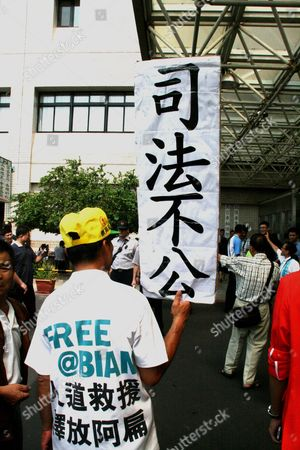 A Supporter of Former Taiwanese President Chen Shui-bian Holds a Placard Reading: 'Justice System is Unfair' and Wearing a T-shirt with the Words 'Free @ Bian' (referring to Chen's Nickname 'Ah Bian') As Chen is About to Leave the Taoyuan General Hospital After a Medical Checkup in Taoyuan Northern Taiwan on 11 September 2012 Chen President From 2000 Until 2008 is Serving a 17-and-a-half-year Jail Term For Corruption Chen Supporters Were Demanding President Ma Ying-jeou to Release Chen Or Grant Him Medical Parole Saying Chen's Health is Deteriorating and He Might Die in Jail Soon Taiwan Taoyuan