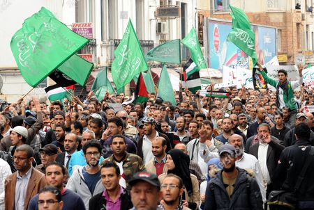 Stock Image of A General View Shows Tunisian Protesters Holding Palestinian and Green Islamic Flags During a Demonstration Called by the Ruling Islamist Party Ennahda Against the Israeli's Attacks in Gaza Strip in Tunis Tunisia 16 November 2012 Several Hundred People Demonstrated in Tunisia on 16 November in Support of the People of Gaza As an Israeli Military Offensive Aimed at Ongoing Rocket Fire From Gaza Entered Its Third Day on 17 November a Delegation Led by Foreign Minister Rafik Abdessalem Will Pay a Visit to Gaza a Day After a Visit by Egyptian Prime Minister Hesham Qandil Tunisia Tunis
